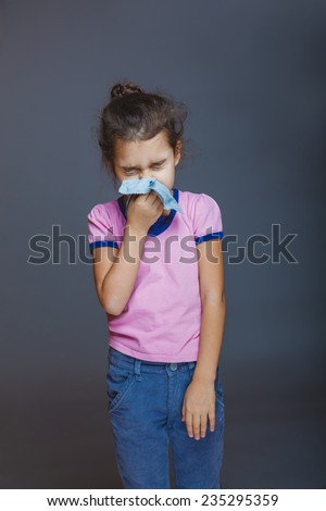 girl blows her nose wrinkled and a handkerchief - stock photo