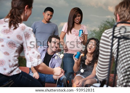 Girl blows out flaming marshmallow with friends outside - stock photo