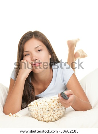 Girl bored watching boring movie in bed. Funny image of woman lying down in bed on White background eating popcorn and zapping changing channel on tv. - stock photo