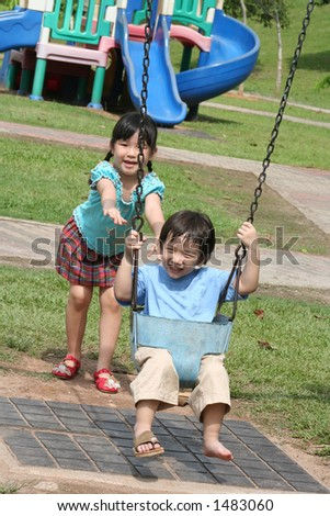 Girl & boy at the park swinging - stock photo