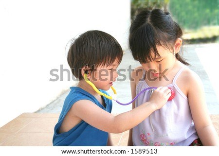 girl & boy playing toy stethoscope at leisure - stock photo