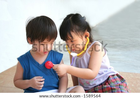 girl & boy playing with doctor's stethoscope toy - stock photo
