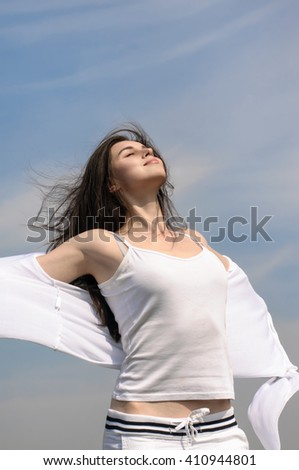 Girl breathes in fresh air on a blue sky background. She stands her arms to the side and her hair fluttering in the wind. Concept: freedom, health, cleanliness. - stock photo