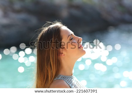 Girl breathing fresh air on a tropical beach on holidays with the sea in the background - stock photo