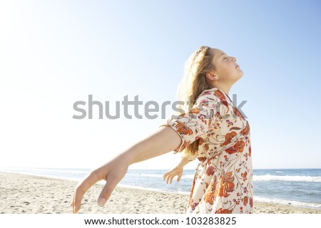 Girl breathing fresh air while standing by the shore on a white sand beach. - stock photo
