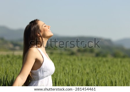 Girl breathing fresh air with white dress in a green wheat meadow - stock photo