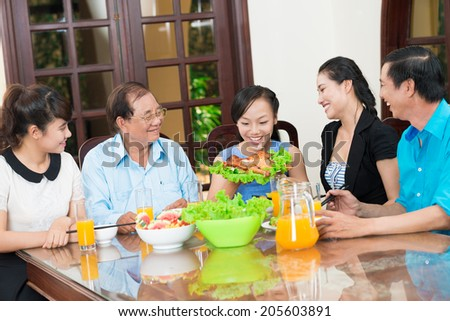 Girl bringing roast chicken to the dinner table - stock photo