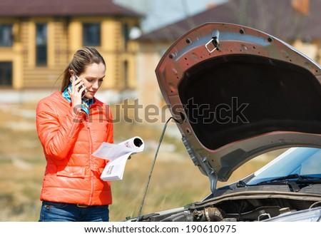 girl broken car with open hood call for help - stock photo