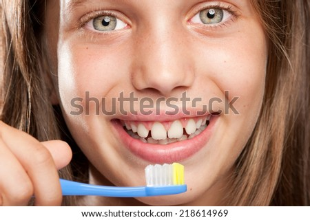 girl brushing her teeth on a gray background - stock photo
