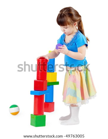Girl build a tower of toy bricks on a white background - stock photo