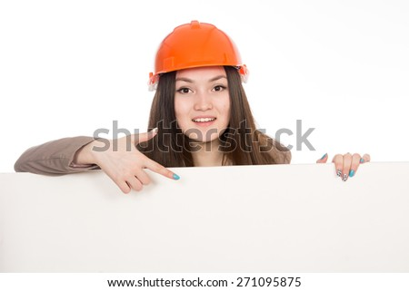 Girl builder in helmet showing a finger on a blank banner. Asian cheerful young female model displays ads. Isolated on a white background - stock photo