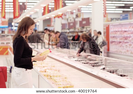 Girl buys a hen in a supermarket - stock photo