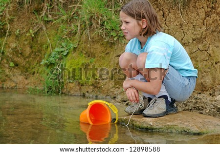 girl by river catching fish - stock photo