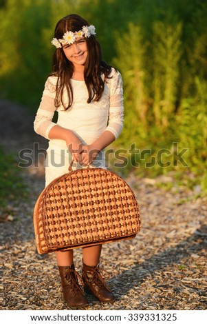 girl carrying vintage picnic basket - stock photo
