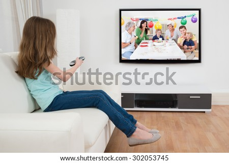 Girl Changing Channel With Remote Control In Front Of Television At Home - stock photo