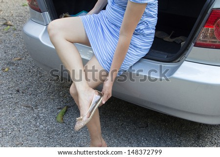 Girl changing shoes at the end of the car.