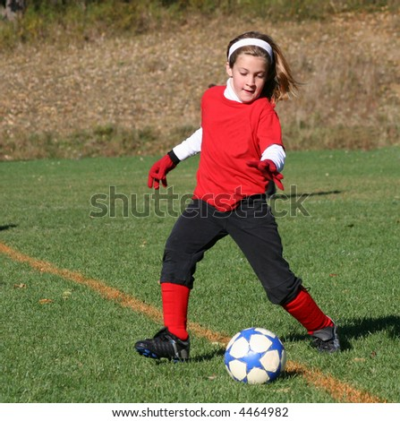 Girl Chasing Ball on Soccer Field - stock photo