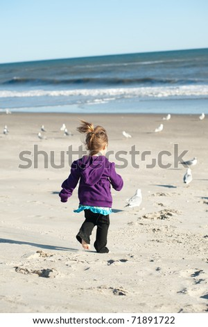 girl chasing birds at the beach - stock photo