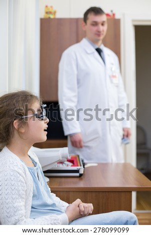 girl checks sight at the reception of an ophthalmologist - stock photo