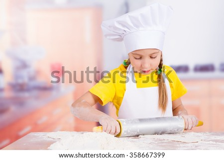 girl chef holding a rolling pin in hand, on a table egg, flour, butter, milk - stock photo
