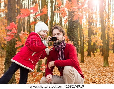 Girl child and father taking outdoor photo with mobile phone in an autumn park - enjoying modern technology - stock photo