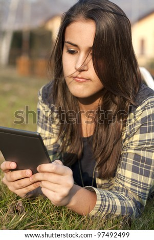 Girl/child reading a e-book in a meadow - stock photo