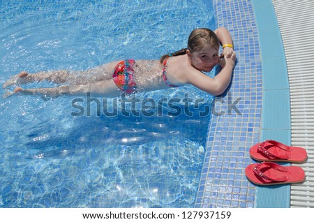 Girl child relaxing in tropical pool - stock photo