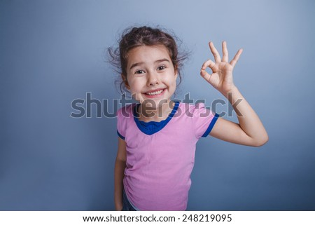 girl child six years of European appearance showing thumbs up ok on a gray background - stock photo