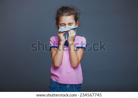 girl child sneezes into a handkerchief on a gray background - stock photo