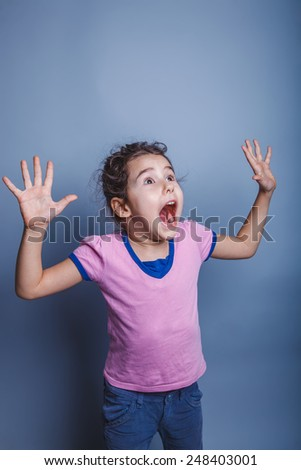 Girl Child Teen seven years, European appearance brunette raised her hands and opened her mouth on a gray background, happiness - stock photo