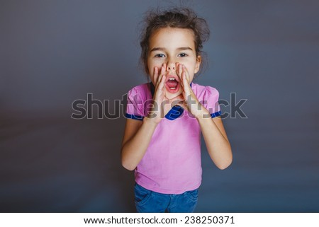 Girl Child Teen 7 years, European appearance brunette cries leaning his hands to his mouth on a gray background - stock photo