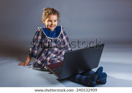 Girl child teenager European appearance brunette looking at a computer monitor and experiences happiness and joy on a gray background - stock photo