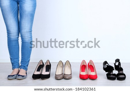 Girl chooses shoes in room on grey background