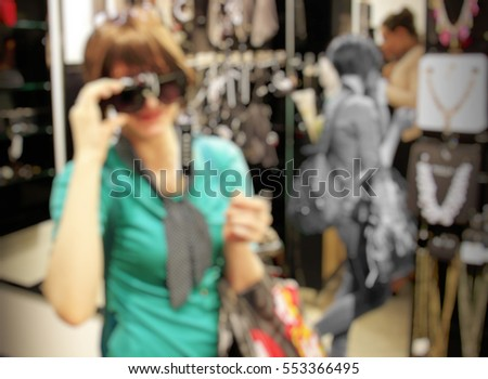 Girl chooses sunglasses in store. Blurred background