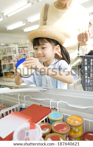 girl choosing ice cream at convenience store