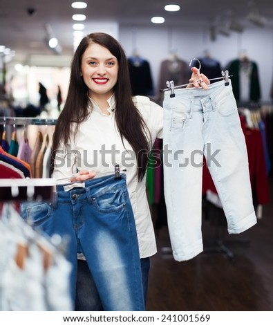 Girl choosing jeans at clothing store - stock photo