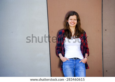 Girl city portrait. Woman smiling outside in evening light by the wall. Beautiful young smiling Caucasian woman. - stock photo