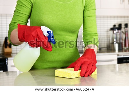 Girl cleaning kitchen  with sponge and rubber gloves - stock photo