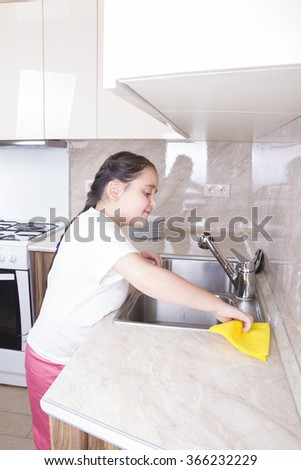 Girl cleans the sink yellow cloth