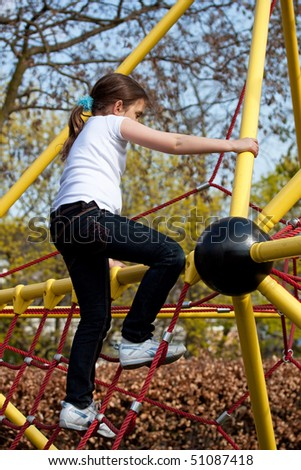 Girl climbing a yellow frame in a playground - stock photo