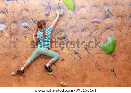 Girl climbing on practical wall indoor, bouldering training - stock photo