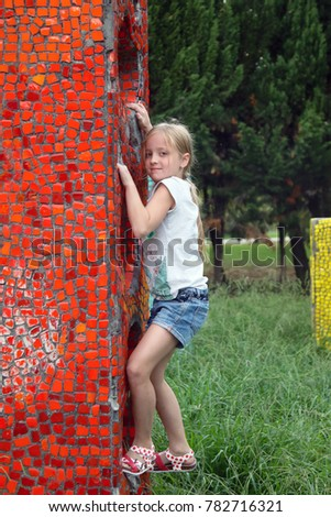 Girl climbing on the wall in the park.
