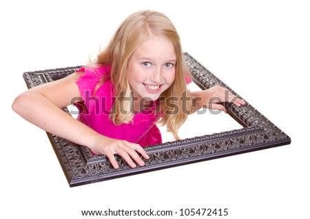 Girl climbing through a picture frame, isolated on white - stock photo