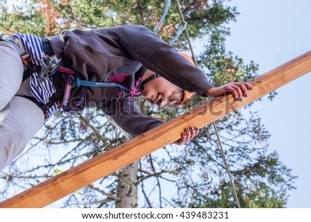 girl climbs into ropes course. Fearfully