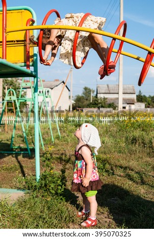 Girl climbs on the rings sports game complex, and another girl standing below and looking up - stock photo
