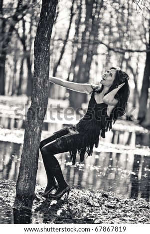 girl clings to a tree. Black and white photo