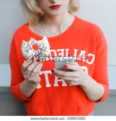 girl close-up of a beautiful young blonde in the street lifestyle on  background with red lips smiling in sunglasses  with a red manicure jeans with a telephone selfie hipster eating a donut - stock photo