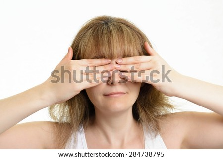 girl closes eyes with her hands - stock photo