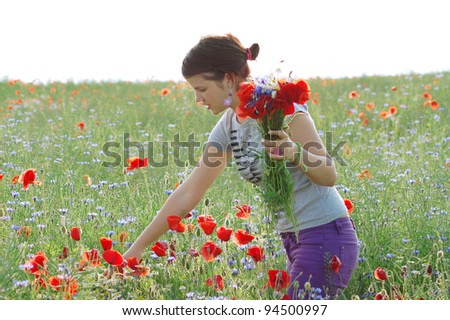 girl collecting poppies and cornflower from a summer field. - stock photo