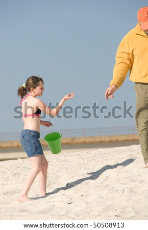Girl collecting seashells with father on beach - stock photo